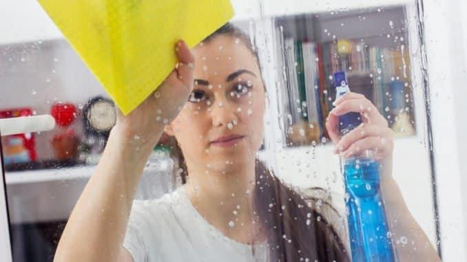 Junge Frau beim Fensterputzen ohne Fensterputzgerät