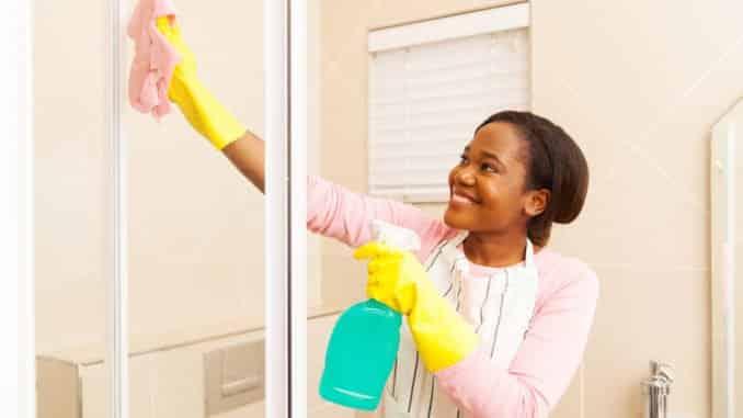 Junge afrikanische Frau putzt die Duschtür