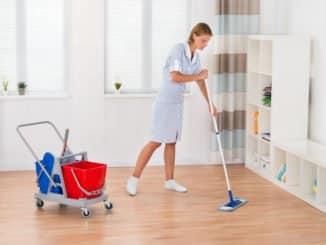 Junge Putzfrau wischt den Fußboden