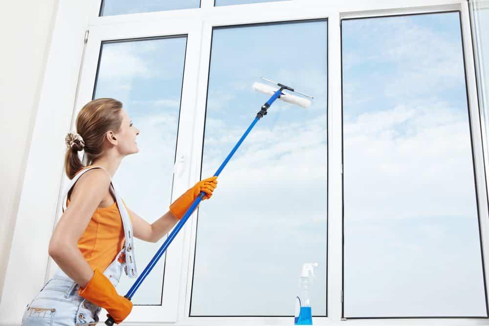 Junge Frau putzt eine große Fensterfläche