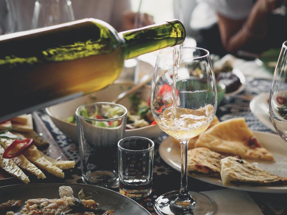 Essenstisch mit Speisen und einem Weißwein