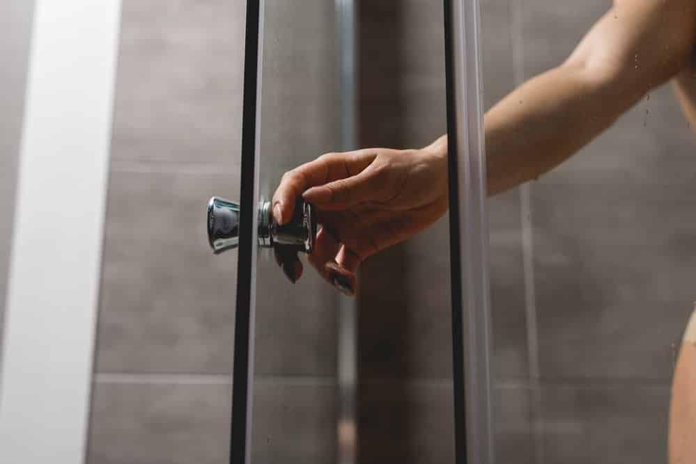 Frau öffnet Duschkabinentür