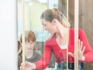 Frau und Tochter betrachten eine Duschschiebetür