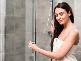 Junge Frau prüft die Duschkabinendichtung