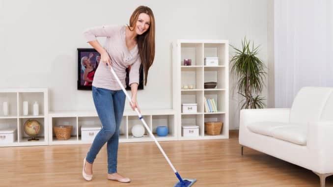Junge Frau wischt den Fußboden