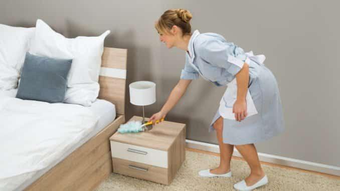 Zimmermädchen benutzt einen Staubwischer