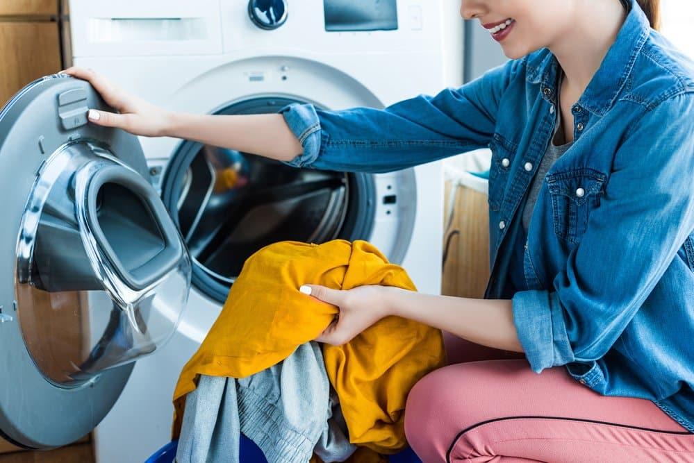 Frau hockt vor Waschmaschine ohne Waschmaschinenerhöhung