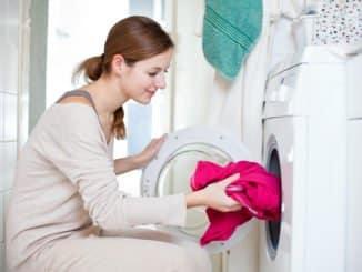 Junge Frau hockt vor Waschmaschine ohne Waschmaschinenpodest