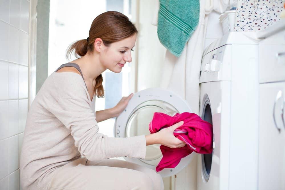 Junge Frau füllt ihre Waschmaschine