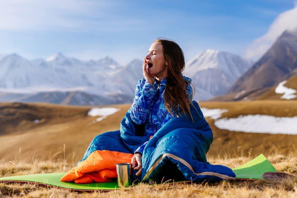 Junge Frau im Daunenschlafsack