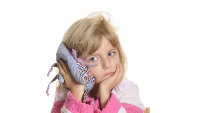 Mädchen mit erwärmtem Kirschkernkissen am Ohr