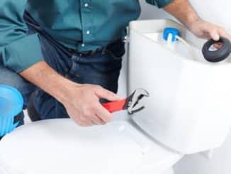 Klempner beim Spülkasten entkalken