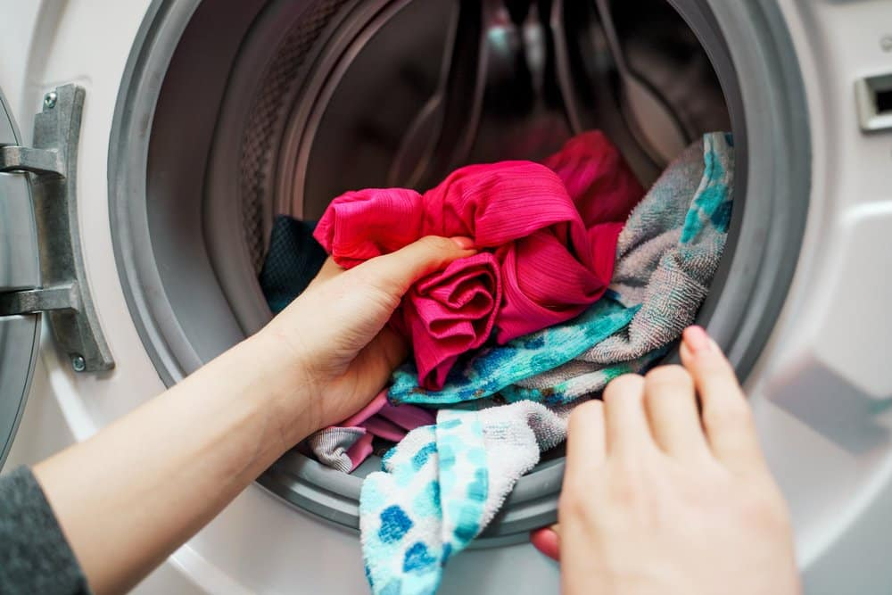 Waschmaschine wird mit dreckiger Wäsche gefüllt