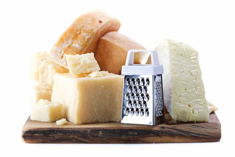 Verschiedene Käse mit manueller Käsereibe