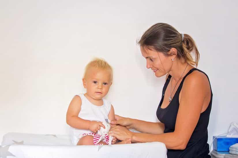Baby wird auf einem Waschmaschinen Wickelaufsatz gewickelt