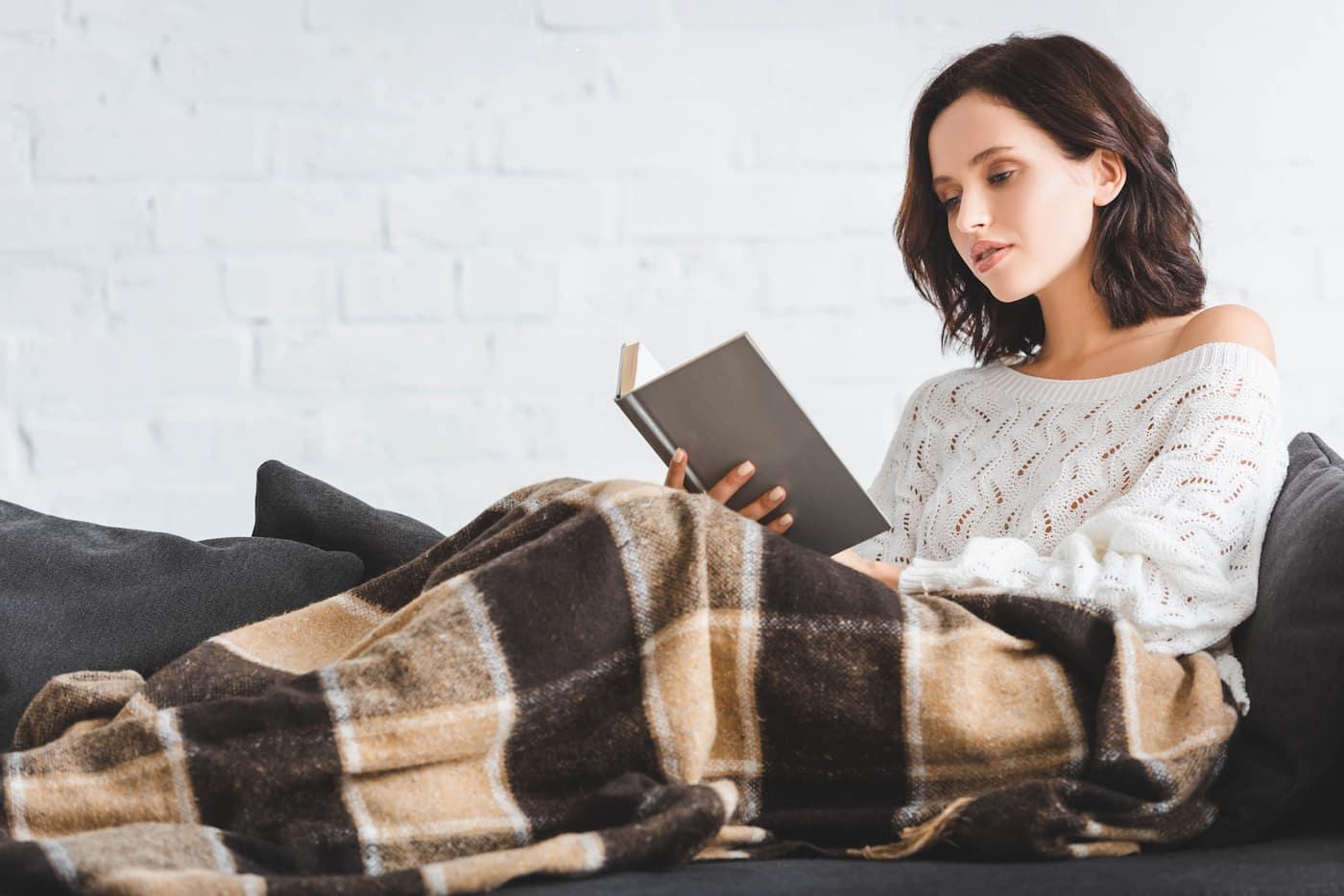 Eine Decke mit Ärmeln schafft Bewegungsfreiheit beim Lesen