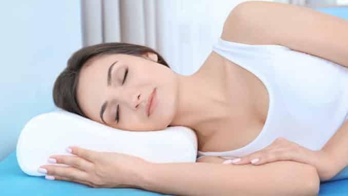 Frau schläft auf einem orthopädischen Kopfkissen