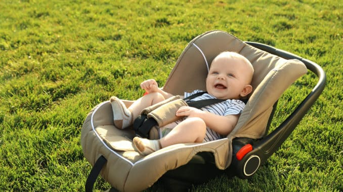 Babyschale auf dem Rasen mit lachendem Baby