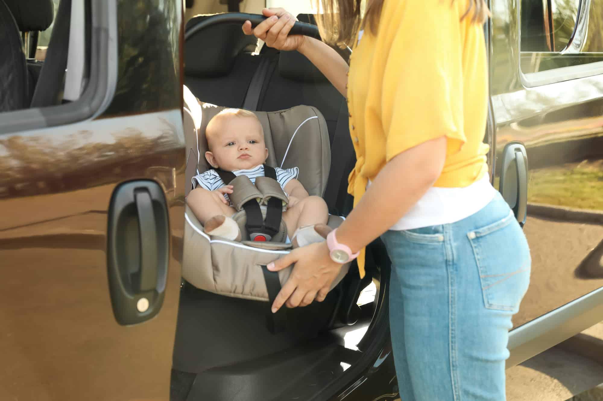 Frau befestigt eine Babyschale samt Baby im Auto