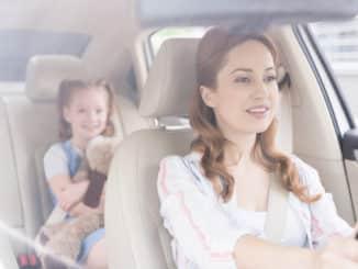 Kind auf der Rückbank auf einer aufblasbaren Sitzerhöhung