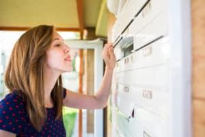 Eine Frau schaut durch den Briefschlitz eines Durchwurfbriefkastens im Mehrfamilienhaus.