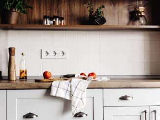 Küchenzeile als Nahaufnahme in hellgrau und Holz mit Küchenabschlussleiste