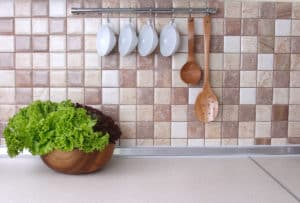 Küchenarbeitsplatte und -Wand mit Küchenabschlussleiste dazwischen, Salat auf der Platte und Küchenutensilien an der Wand