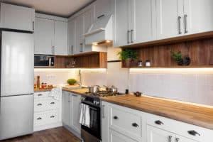 Küchenzeile in hellgrau und Holz mit Küchenabschlussleiste