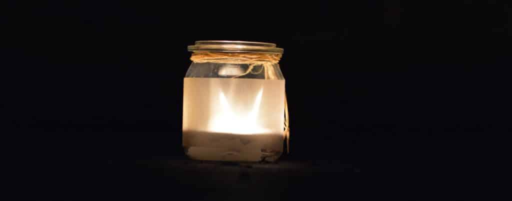 Kerze im Marmeladenglas leuchtet in der Dunkelheit.