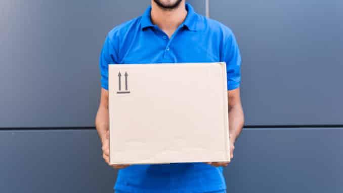 Zusteller hält Paket in der Hand