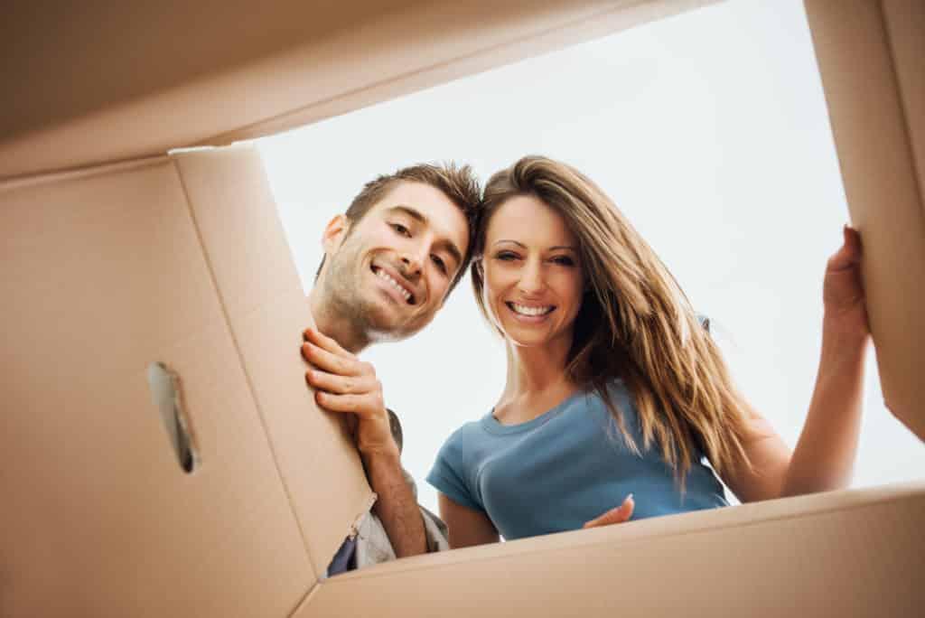 Zwei Personen schauen in ein geöffnetes Paket hinein.