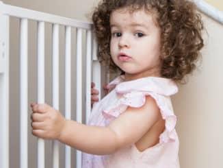 Ein Kind steht umfasst stehend die Stäbe eines Treppenschutzgitters im Treppenhaus.