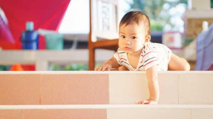 Ein Baby versucht, Treppenstufen hinunterzukrabbeln.