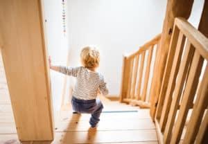 Ein Kleinkind geht unsicher allein eine steile Treppe hinab.
