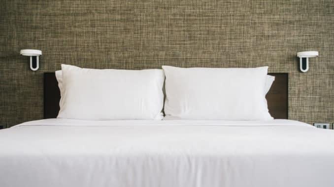 Ein weiß bezogenes Bett mit schwarzem Kopfteil steht vor einer grauen Wand.