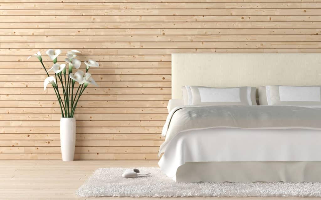 Ein weißes Bett mit grauer Tagesdecke steht im Schlafzimmer vor einer hellen Holzwand auf einem weißen Teppich und daneben steht eine Vase mit weißen Blumen.